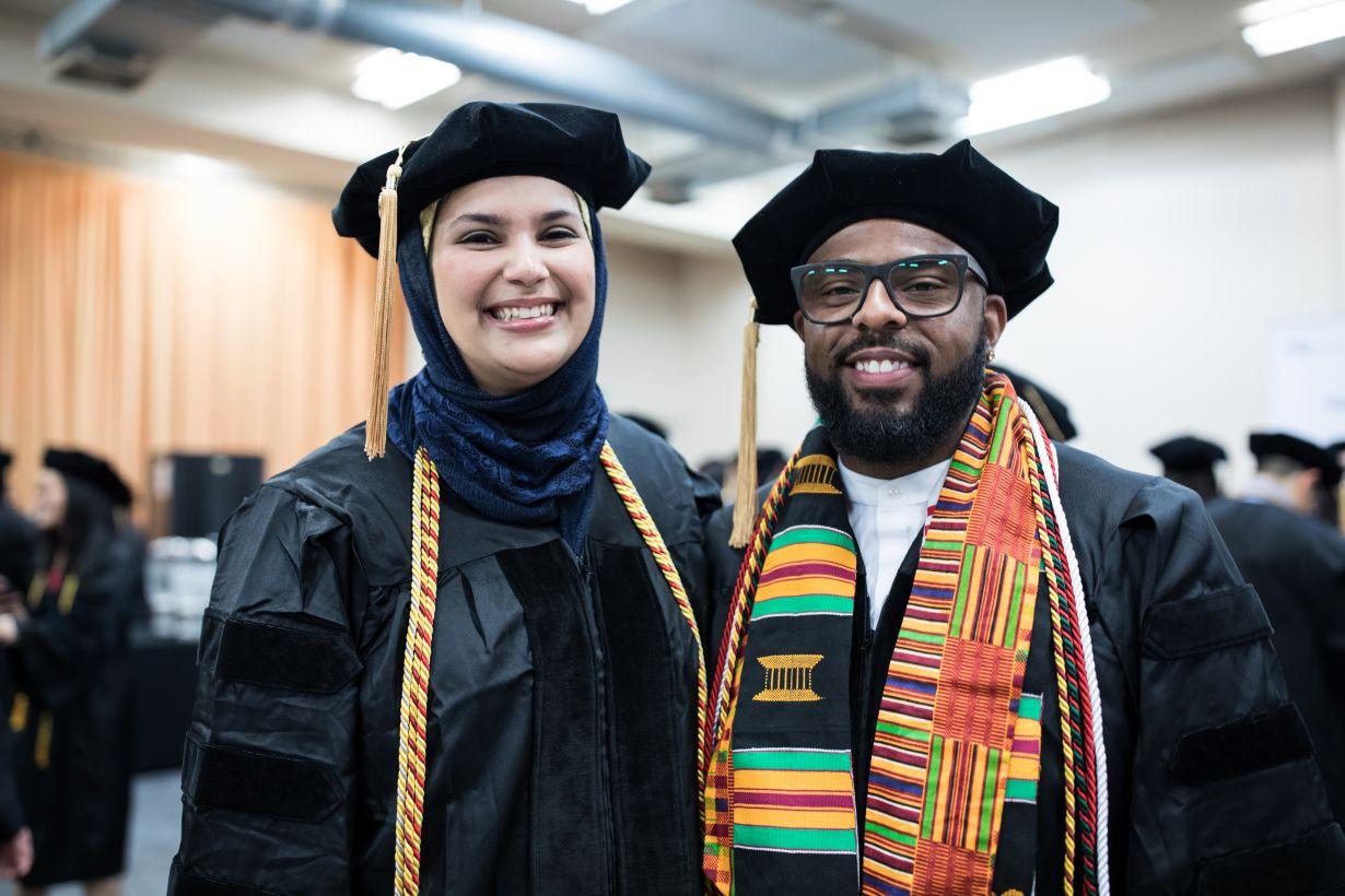 two graduates in full regalia.