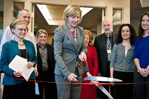 Desmond-Hellmann cuts a red ribbon with giant scissors while others watch