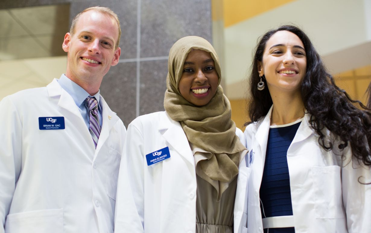 three students in white coats