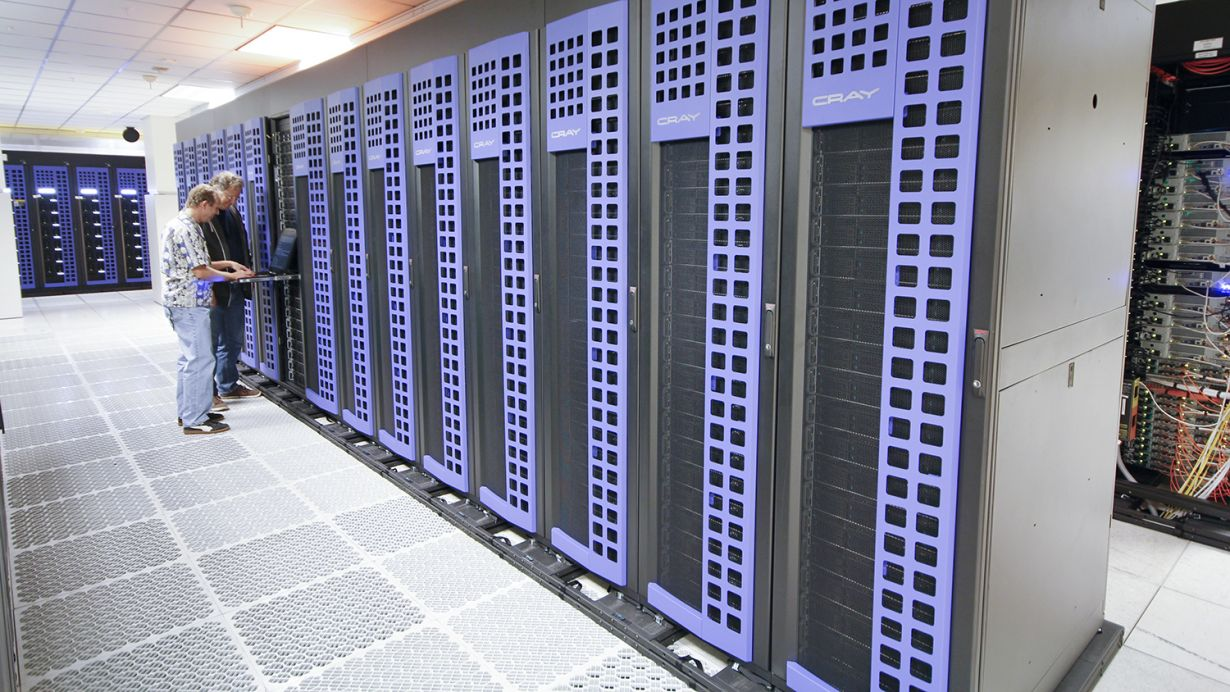 two people stand next to a Cray supercomputer