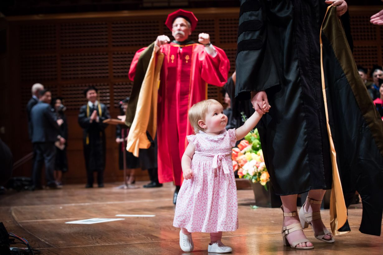 a graduate and her toddler walk across the stage together.