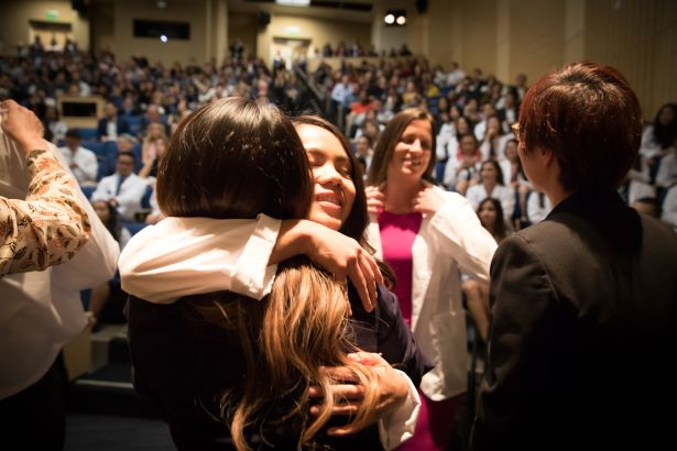 PharmD student celebrates after the White Coat Ceremony with family
