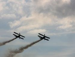 two bi-planes viewed against bright clouds