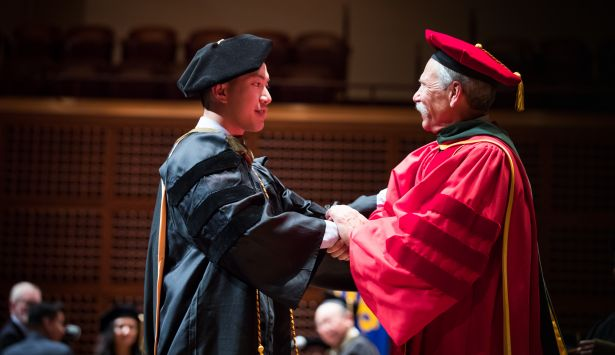 graduate and Guglielmo dressed in regalia