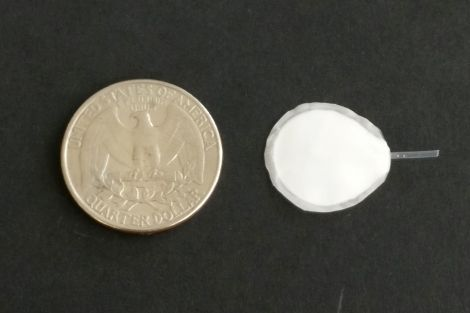 device alongside a quarter to show size