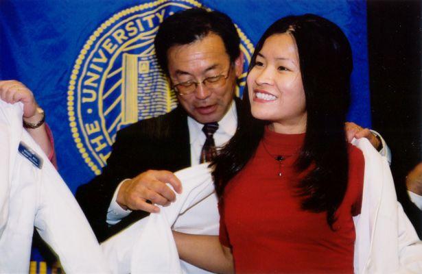 Kishi helps student with white coat