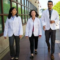 students wearing white coats and walking