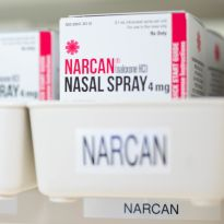 Boxes of Narcan are shown on a shelf in a pharmacy.