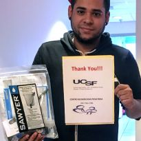 staff member holds one water filter and a thank you note.