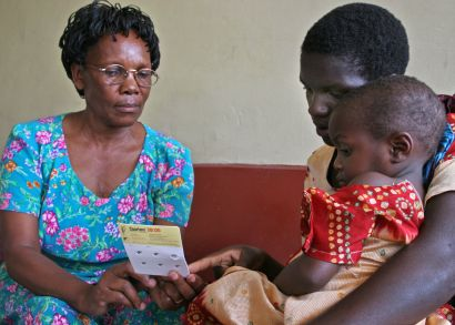 seated child, parent, and nurse examine a small sheet of paper