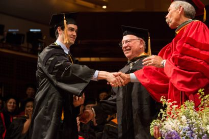 graduate receives diploma with handshake from the dean