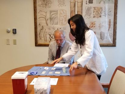 Agustin, standing, with Guglielmo, seated at table with vaccine materials