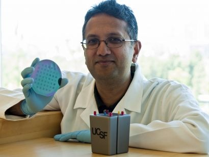Shuvo Roy holds a silicon filter wafer next to a prototype of the artificial kidney