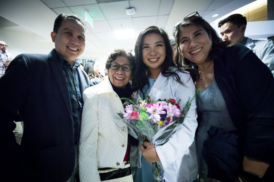 A PharmD student poses with her family after the White Coat Ceremony