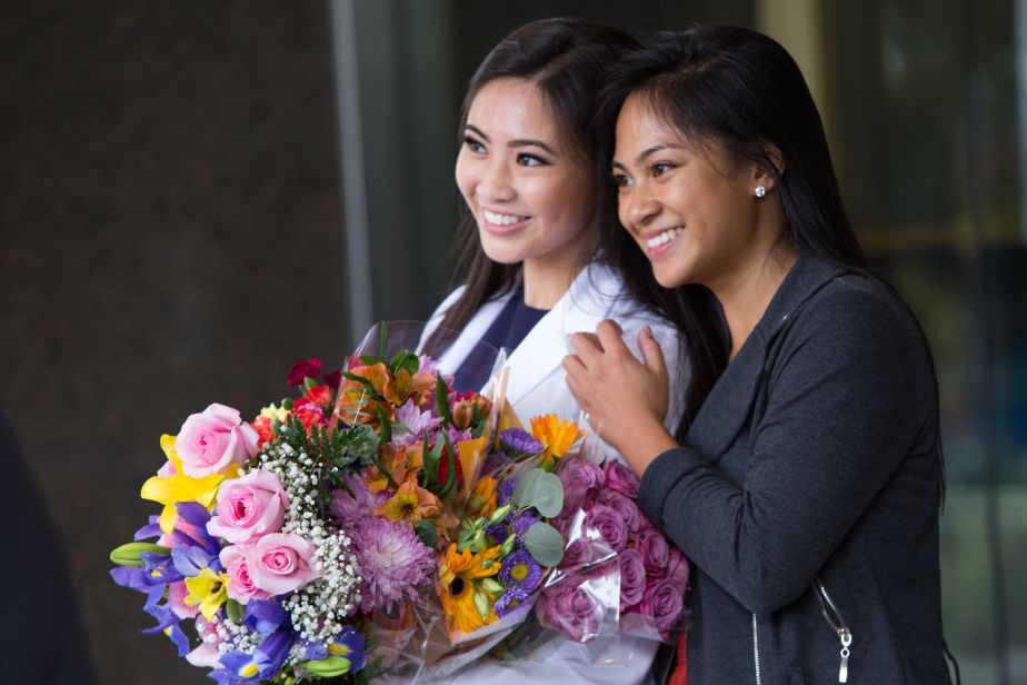 A PharmD student poses with a family member after the White Coat Ceremony