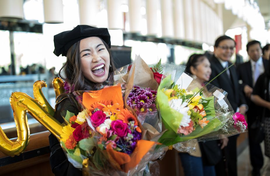 graduate with balloons and flowers